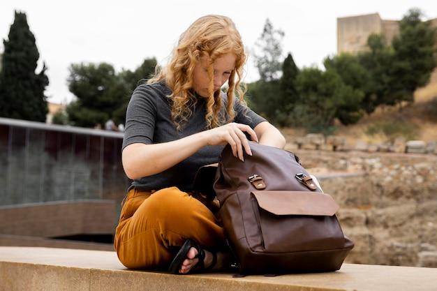 Frau, die im rucksack sucht