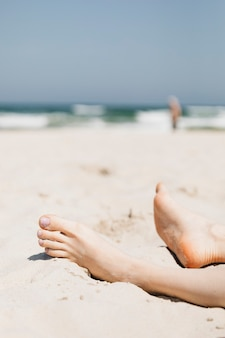 Frau, die im sand an einem strand entspannt