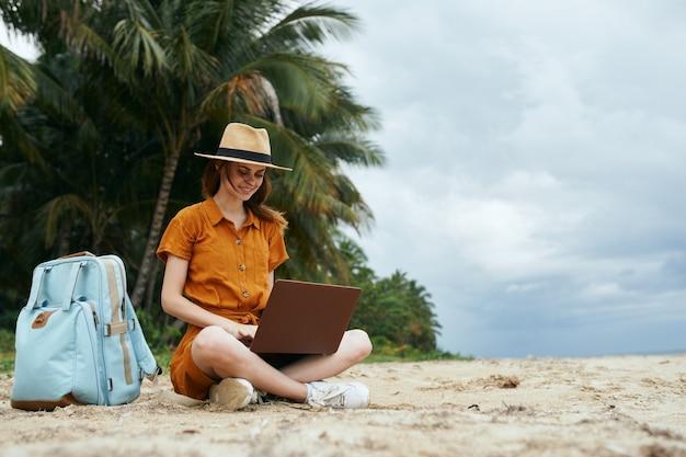 Frau, die im sand vor einem laptop auf dir strand sitzt