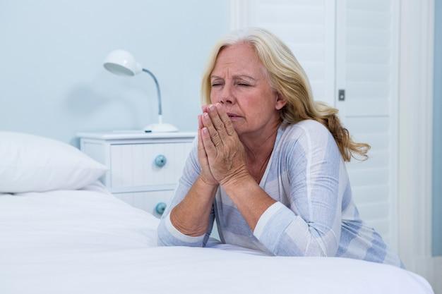 Frau, die im schlafzimmer betet