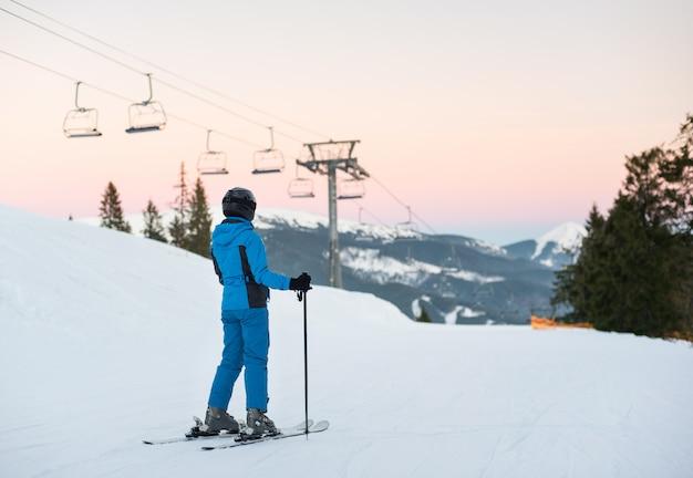 Frau, die im schneeberg gegen einen skilift steht