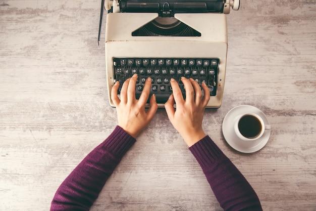 Frau, die im schreibmaschinenhandkaffee arbeitet