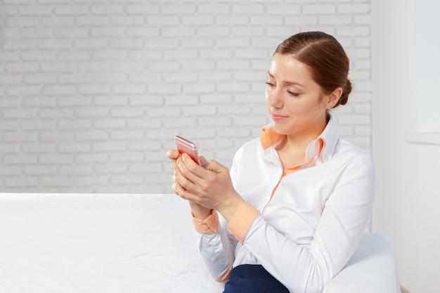 Frau, die im sofa spricht am mobiltelefon sich entspannt