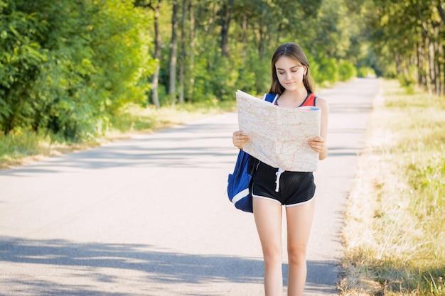 Frau, die im sommer nach wegbeschreibungen auf der karte sucht