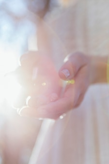 Frau, die im sonnenlicht ihre hände hält