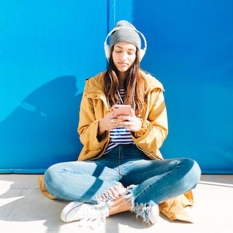 Frau, die im sonnenlicht vor tür unter verwendung der tragenden kopfhörer des mobiltelefons sitzt