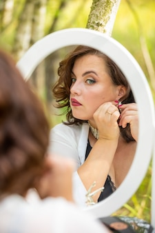 Frau, die im spiegel im wald sitzt und schaut