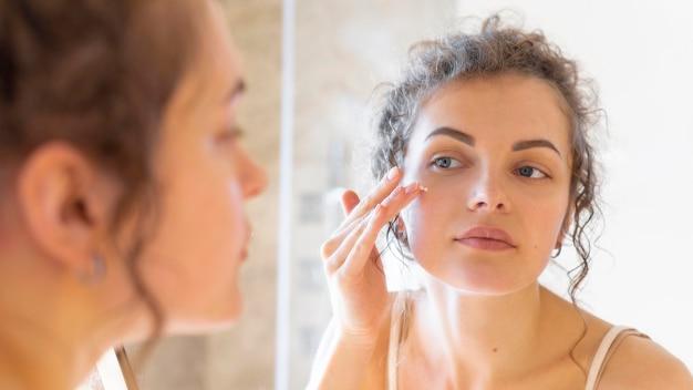Frau, die im spiegel schaut und creme auf gesicht aufträgt