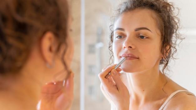 Frau, die im spiegel schaut und lippenstift anwendet