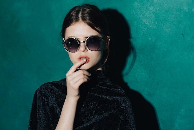 Frau, die im studio, modebrille aufwirft.
