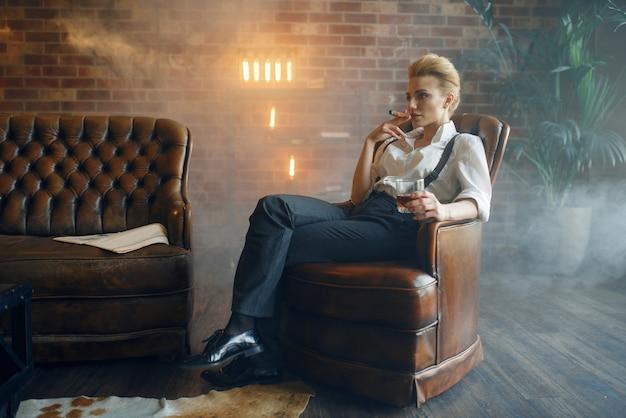 Frau, die im stuhl mit whisky und zigarre sitzt