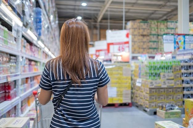 Frau, die im supermarkt mit unschärfegeschäft einkauft