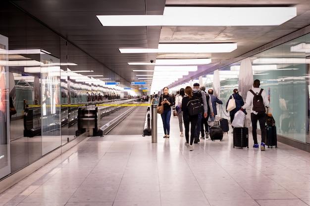 Frau, die im terminalflughafen mit der gruppe des passagiergehens steht.