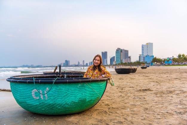 Frau, die im traditionellen bambuskorbboot vietnams auf dem strand bei da nang, vietnam sitzt.