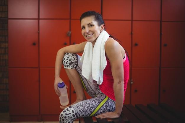 Frau, die im umkleideraum der turnhalle nach dem training sitzt