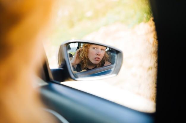 Frau, die im vorderansichtspiegel im auto schaut