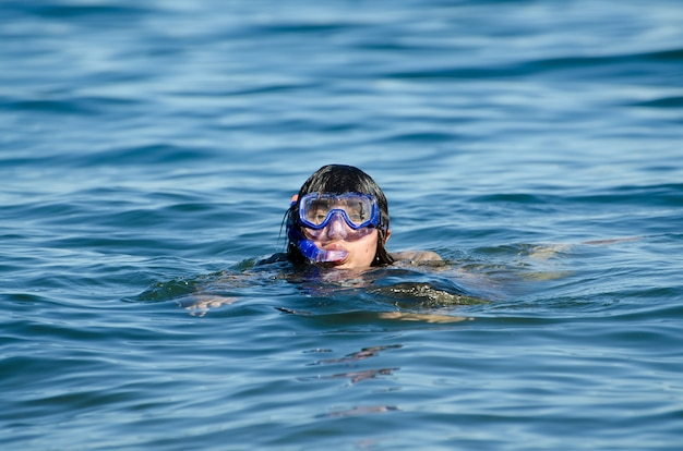 Frau, die im wasser mit einer tauchmaske schwimmt
