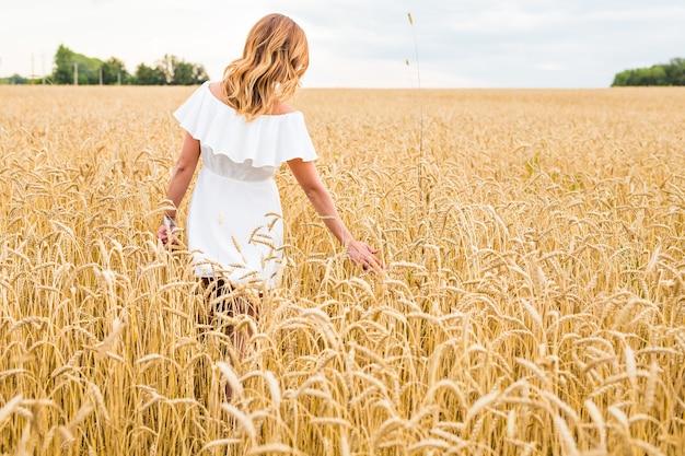 Frau, die im weizenkonzept über naturlandwirtschaft und -leute geht