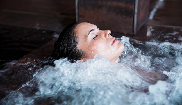 Frau, die im whirlpool sich entspannt