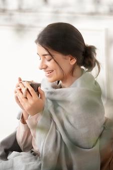 Frau, die im winter einen schluck tee aus der tasse trinkt