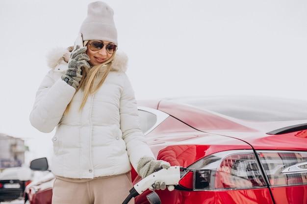 Frau, die im winter rotes elektroauto auflädt