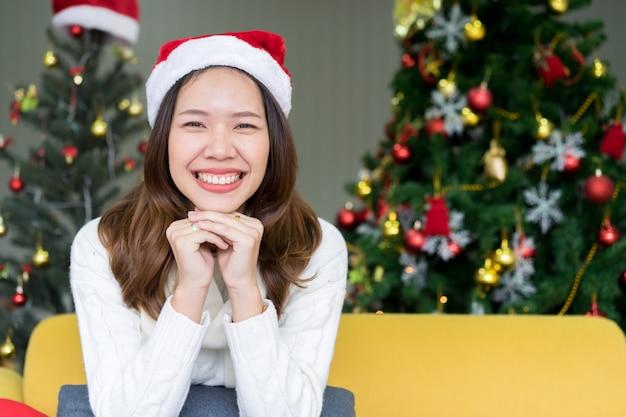 Frau, die im wohnzimmer für frohe weihnachten und guten rutsch ins neue jahr-festival lächelt