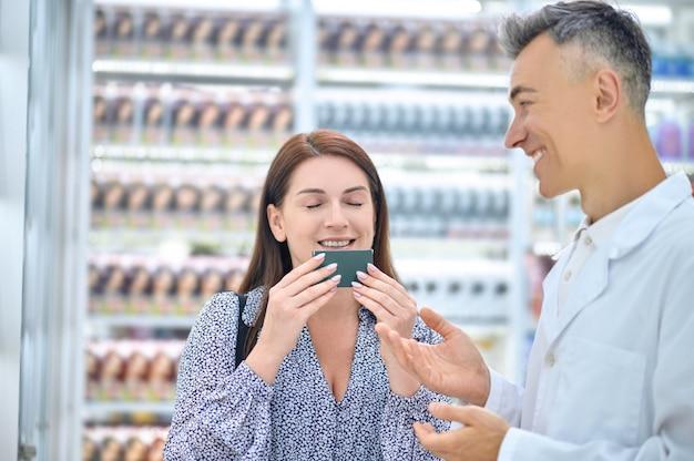 Frau, die in anwesenheit eines apothekers ein hautpflegeprodukt auswählt