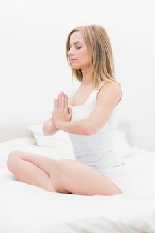 Frau, die in betende position auf bett sitzt