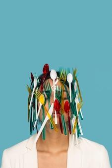 Frau, die in buntem plastikgeschirr bedeckt wird