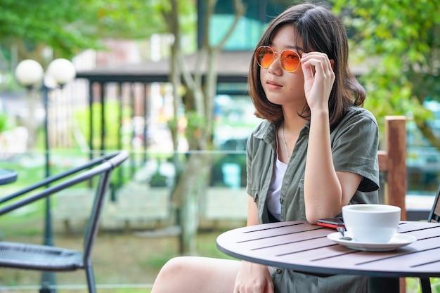 Frau, die in caféterrasse mit kaffeetasse sitzt