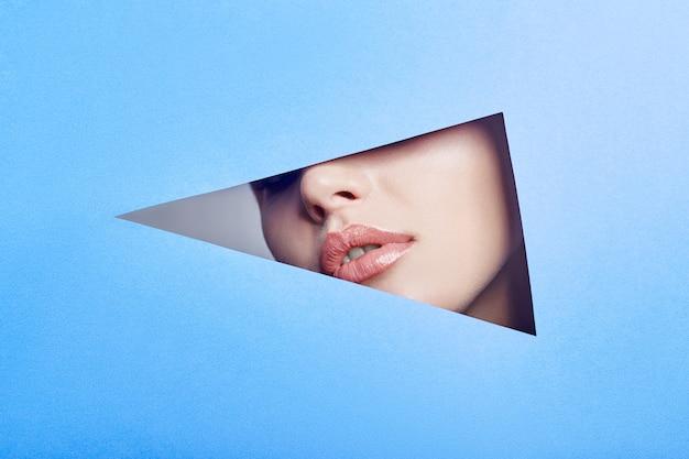 Frau, die in das loch schaut, helles schönes make-up, große augen und lippen, heller lippenstift, professionelle kosmetik und gesichtspflege