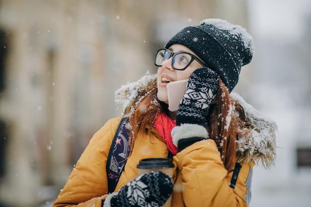 Frau, die in das winter strrt geht und am handy spricht