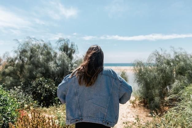 Frau, die in den bäumen nahe tropischem strand steht
