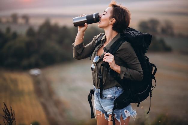Frau, die in den bergen und im trinkwasser wandert