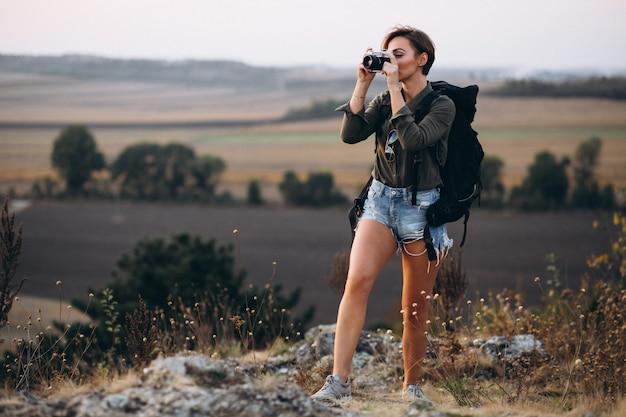 Frau, die in den bergen wandert und foto macht