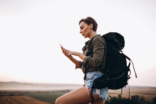 Frau, die in den bergen wandert und kartentelefon verwendet