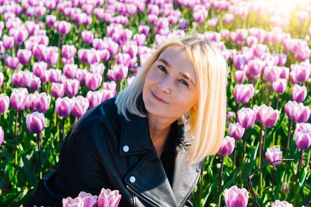 Frau, die in den bunten tulpenblumenfeldern in der region amsterdam, niederlande sitzt. magische niederländische landschaft mit tulpenfeld in holland.