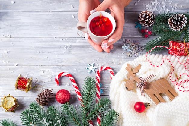 Frau, die in den händen heißen weihnachtstee mit zuckerstange gegen dekorationen, geschenkboxen hält