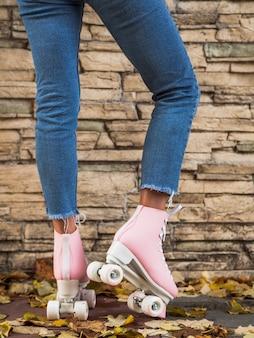 Frau, die in den jeans mit rollschuhen aufwirft