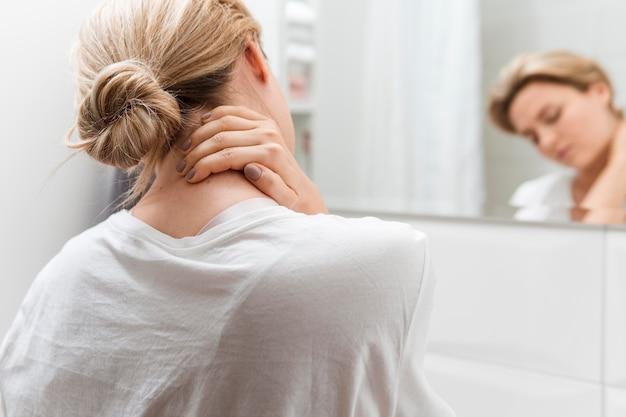 Frau, die in den spiegel schaut, der nackenschmerzen hat