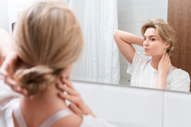 Frau, die in den spiegel schaut