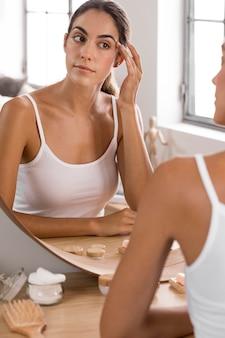 Frau, die in den spiegel selbstpflegekonzept schaut