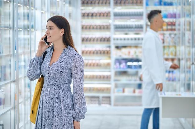 Frau, die in der apotheke auf dem smartphone spricht