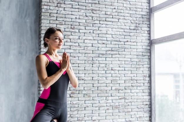 Frau, die in der baumyogahaltung meditiert
