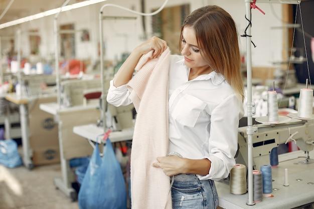 Frau, die in der fabrik mit einem thread steht