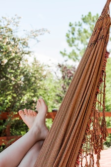 Frau, die in der hängematte auf terrasse im sommer liegt