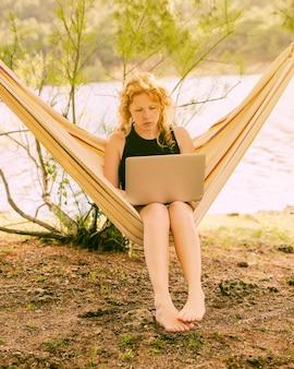 Frau, die in der hängematte mit laptop sitzt