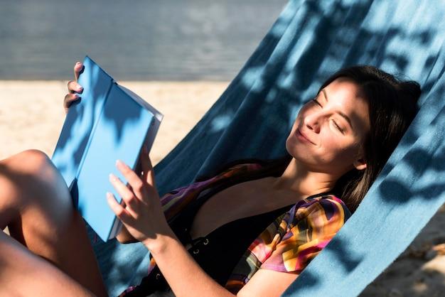 Frau, die in der hängematte während am strand entspannt