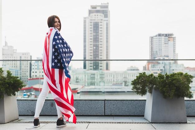 Frau, die in der halben drehung mit großer usa-flagge steht