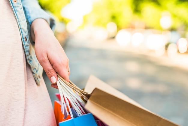 Frau, die in der hand bunte einkaufstaschen hält